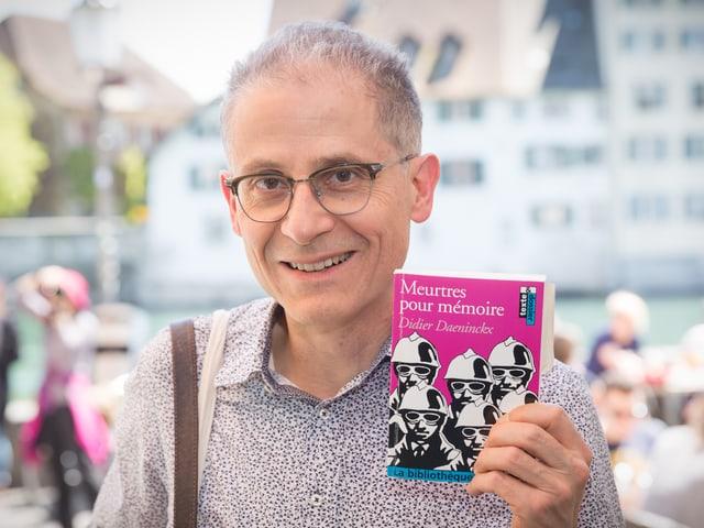 Mann mit Brille, der lächelnd ein Bild in die Kamera hält. Auf dem Buch sind mehrere gezeichnete Soldaten zu sehen.