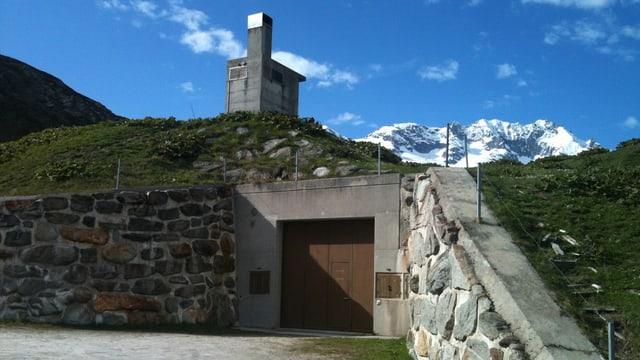 Eingangstor und Lüftungskamin zu einer unterirdischen Unterkunft in den Bergen.