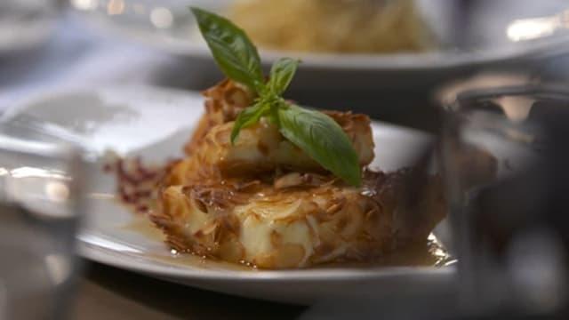 Fetakäse mit Mandeln gebraten auf einem Teller drapiert und garniert.