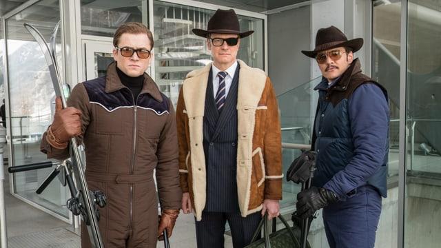 Drei Männer stehen vor einem Glasgebäude, sie tragen warme Kleidung, einer hat ein Paar Ski in der Hand. Der Mann in der Mitte trägt eine Brille mit einer abgedunkelten Scheibe.