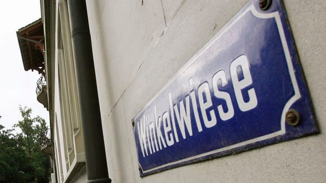 """Hausfassade in Zürich mit dem Strassenschild """"Winkelwiese"""" darauf."""