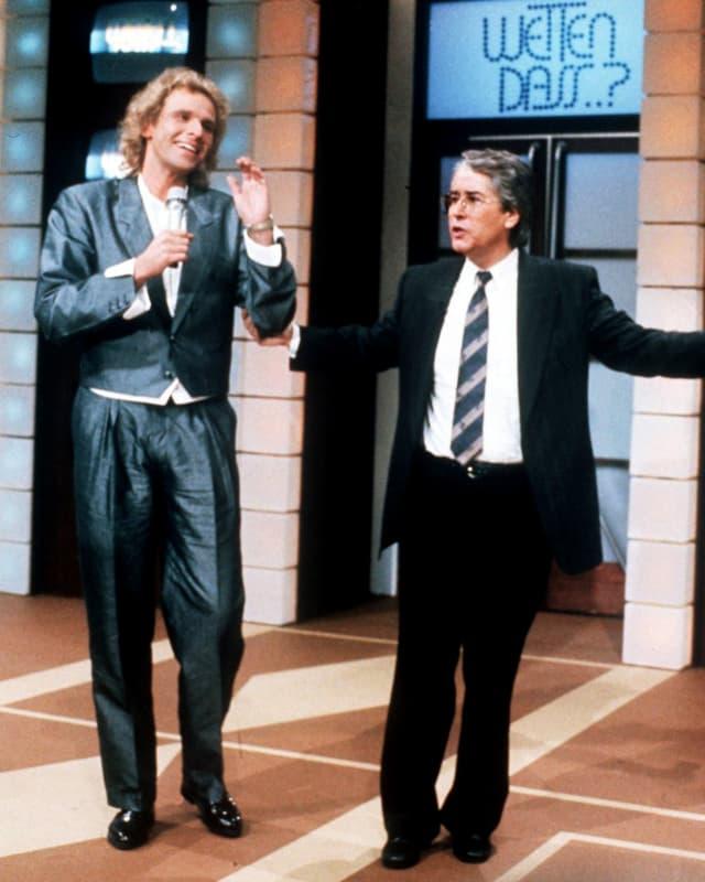 Im Studio: Links Thomas Gottschalk in silbrigem Anzug, rechts Frank Elstner in schwarzem Anzug.