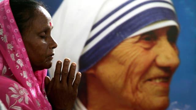 Eine Frau faltet die Hände vor einem Wandbild von Mutter Teresa.