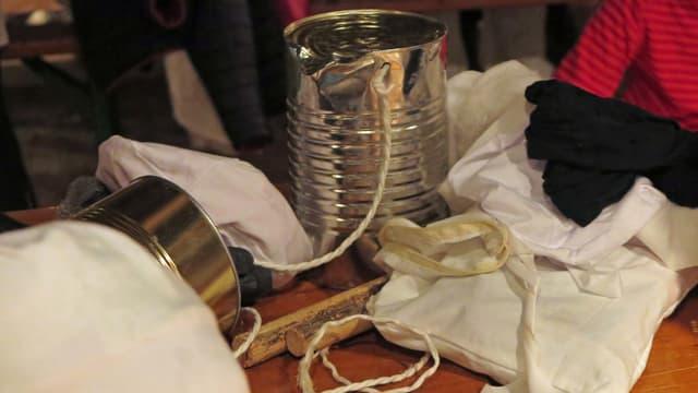 Blechbüchse mit Holzschlägern und Chesslete-Kleidern auf einem Tisch