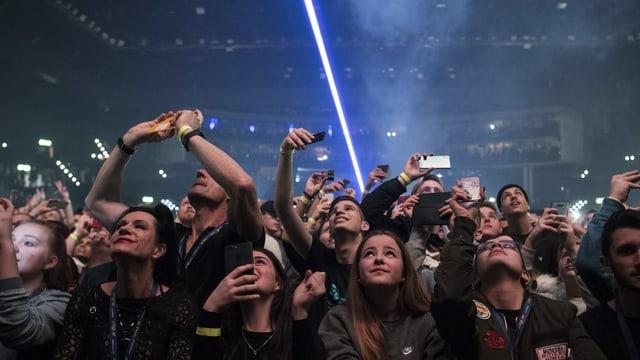 Menschen stehen dicht gedrängt in einer Menge und schauen zur Bühne hoch.