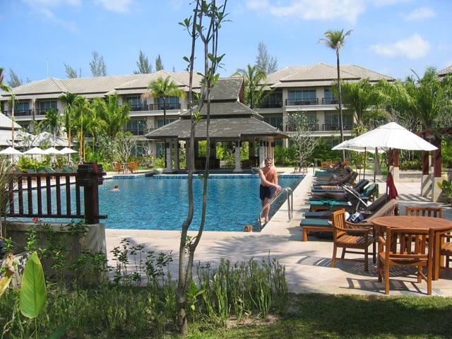 Eine Hotelanlage, eine Person steigt aus dem Wasser, dahinter sind merstöckige Bungalos zu sehen.