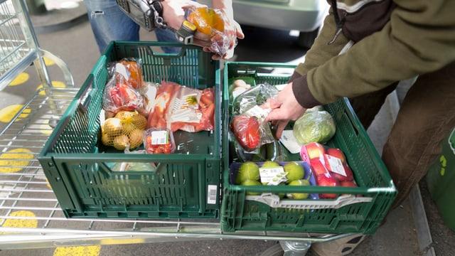 Ein Mann scannt das Etikett eines abgepackten Gemüses, bevor es in eine bereits mit anderen Lebensmitteln gefüllte grüne Kiste gelegt wird.