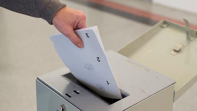 Hand steckt Wahlzettel in Urne