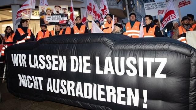 Demonstranten halten ein Plakat hoch: Wir lassen die Lausitz nicht ausradieren.