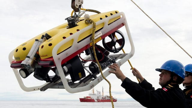 Ein Mann lässt einen Unterwasserroboter über eine Seilwinde ins Wasser
