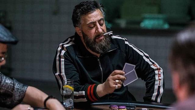 Mann mit Zigarette im Mund am Kartenspielen.