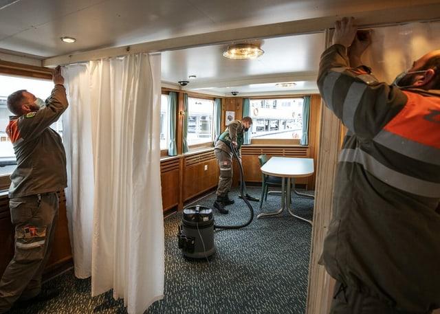 Mitarbeiter des Zivilschutzes installieren Vorhänge und putzen den Teppich