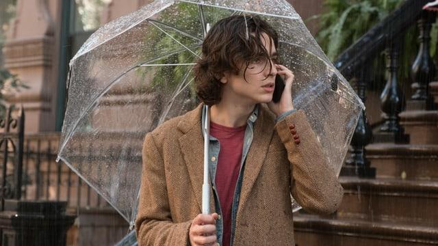 Ein Junge steht unter einem Schirm im Regen.