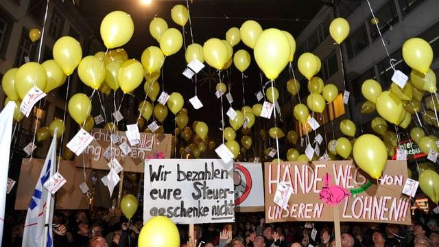 Viele Menschen versammeln sich mit gelben Ballonen und Transparenten