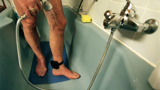 Männerfüsse mit einer Elektronischen Fussfessel in einer Badewann, davor ein Duschschlauch.