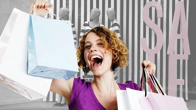 Eine Frau hält jubelnd mehrere Einkaufstaschen in die Höhe.