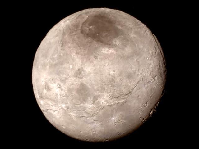 Nahaufnahme des Planeten Charon. In der oberen Polarregion ist eine dunke Fläche zu sehen.