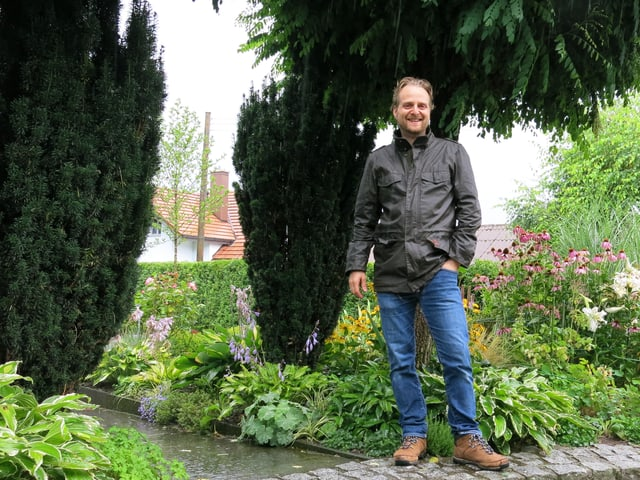 Daniel Auderset steht vor einem von ihm gestalteten Gartenteil.