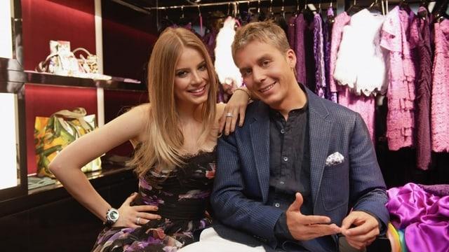 Moderator Reto Scherrer und Xnenia Tchoumitcheva in Abendgarderobe gekleidet mit vollem Kleiderständer im Hintergrund.