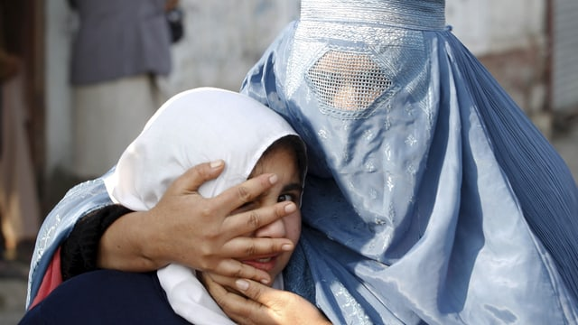 Verhüllte Frau hält ihre Tochter in den Armen