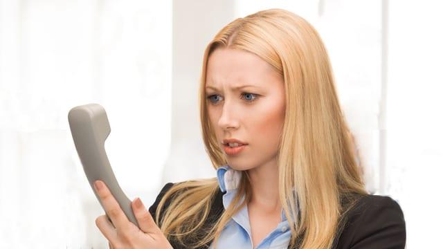 Eine Frau schaut verärgert den Telefonhörer in ihrer Hand an.