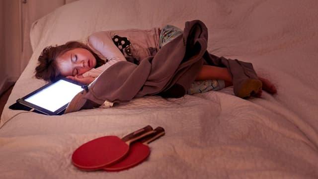 Ein Mädchen schläft mit Tablet neben dem Kopf.