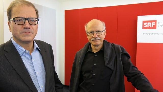Die beiden Politiker stehen im Studio, beide haben eine Brille, der eine einen Schnauz