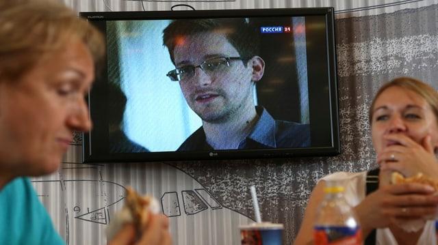 Zwei Personen essen Fastfood. Hinter ihnen leuchtet ein Fernseher, der gerade das Gesicht von Edward Snowden zeigt.