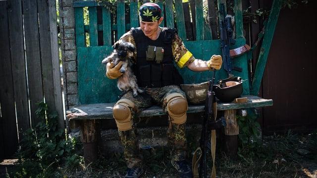 Ein ukrainischer Soldat sitzt auf einer Bank und hält einen Hund in der Hand.