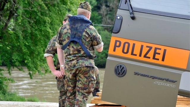 Zwei Soldaten in Unform vor Militärpolizei-Fahrzeug