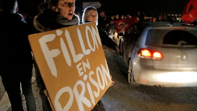 Fillon en Prison - steht auf einem Papschild von Demonstrantinnen.
