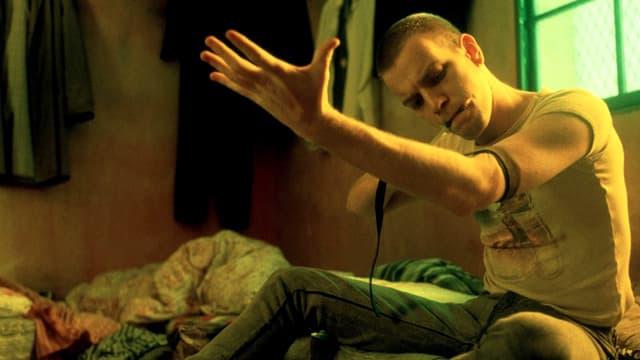 Ein Mann sitzt auf einer Matratze am Boden und setzt sich einen Schuss.
