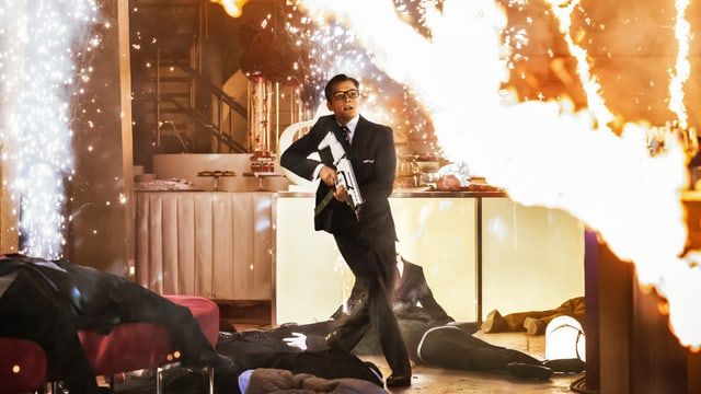 Taron Egerton geht mit einem Maschinengewehr zwischen am Boden liegenden Körpern umher. Im Raum funkt und raucht es.