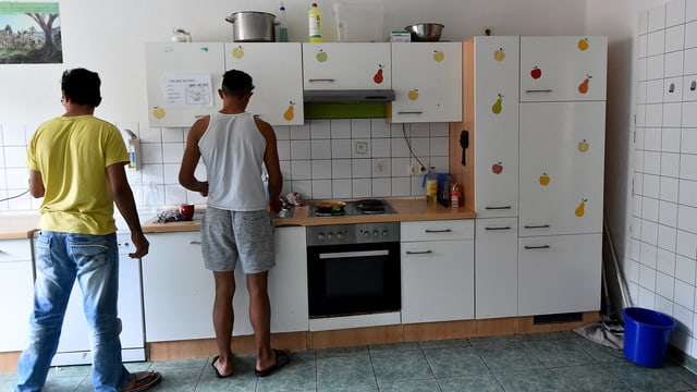 zwei junge Menschen stehen in einer Küche