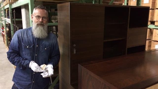 Kurator vor einem alten Möbel - sein Lieblingsstück
