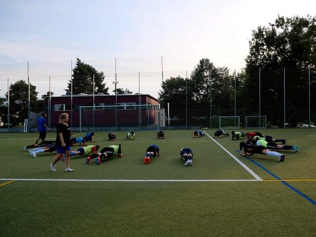 Fussballspieler machen die Brett-Übung