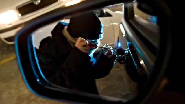 Ein maskierter Mann macht sich an einem Autoschloss zu schaffen, fotografiert via Seitenspiegel des Autos