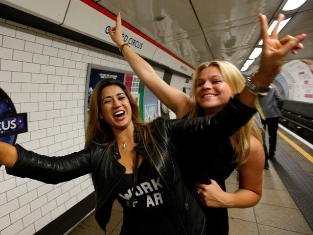 Zwei junge Frauen zeigen das Victory-Zeichen.