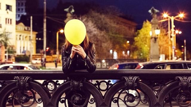 Eine Frau steht auf einer Brücke und hält einen gelben Ballon vor dem Gesicht.