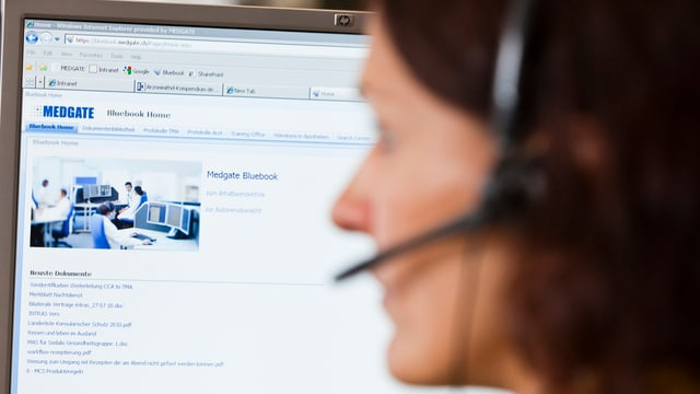 Eine Frau mit Headset an einem Bildschirm mit Medgate-Logo oben links.