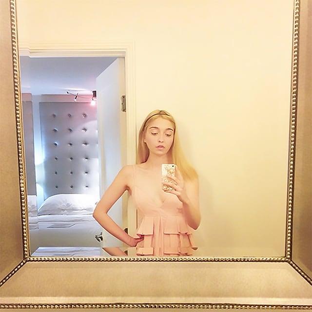 Eine junge Frau fotografiert sich mit dem Smartphine in einem grossen, goldgerahmten Spiegel.