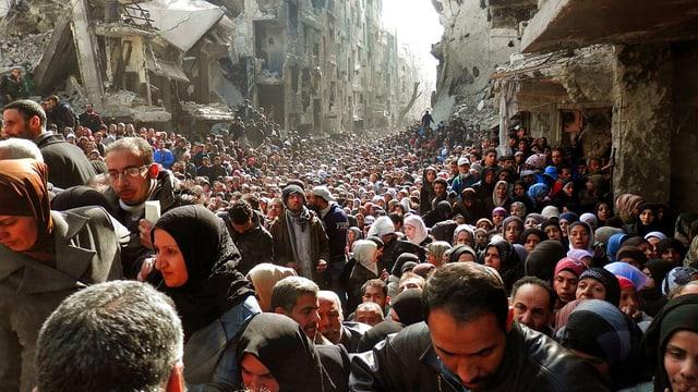 Menschen zwischen zerstörten Häusern.