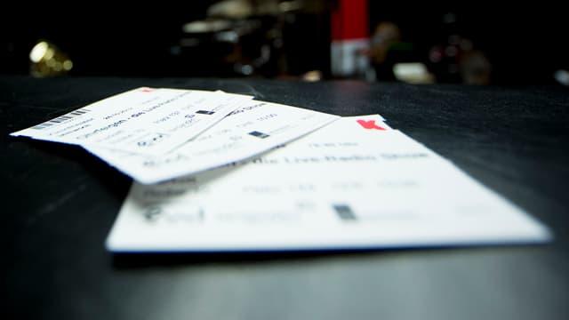 Drei Eintrittskarten liegen auf einem Tisch, im Hintergrund ist ein SRF-Banner erkennbar.