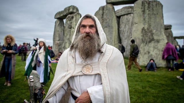 Mann mit grauem Bart, weissem Umhang und Kapuze