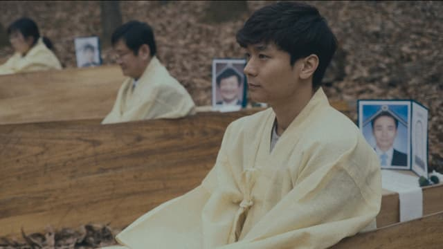 Menschen asiatischer Abstammung sitzen in Holzbänken hintereinander und haben Bild von Angehörigen hinter sich stehen.