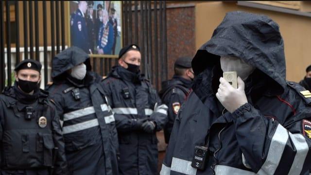 Polizist mit Sprechanlage für Megafon in der Hand.