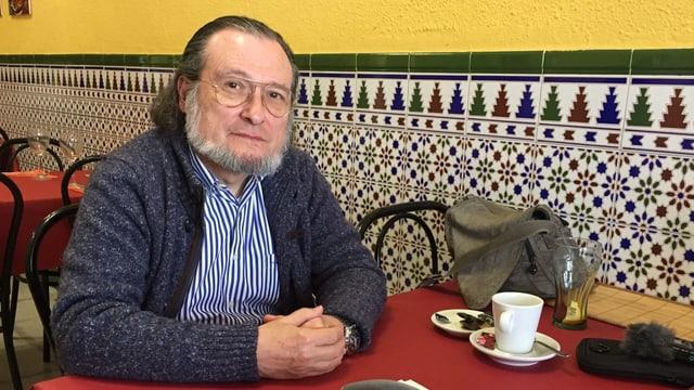 Der Ökonom Santiago Niño Becerra sitzt an einem Tisch. Er hat einen Bart und trägt eine Brille. Vor ihm auf dem Tisch steht eine weisse Kaffeetasse. Der Hintergrund ist recht farbig, das Tischtuch rot.