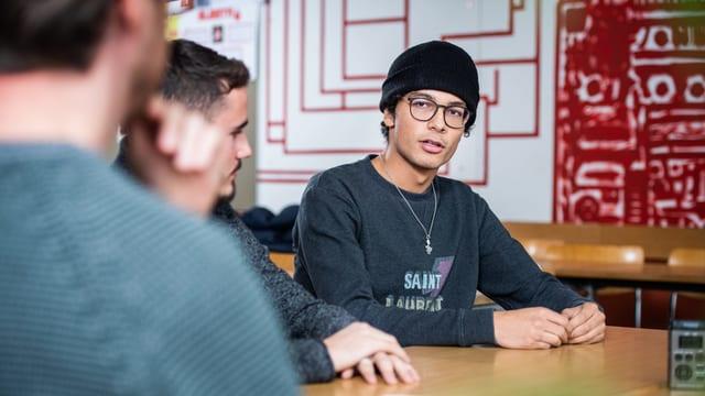 Drei junge Männer nebeneinander an einem Tisch, in ein Gespräch vertieft