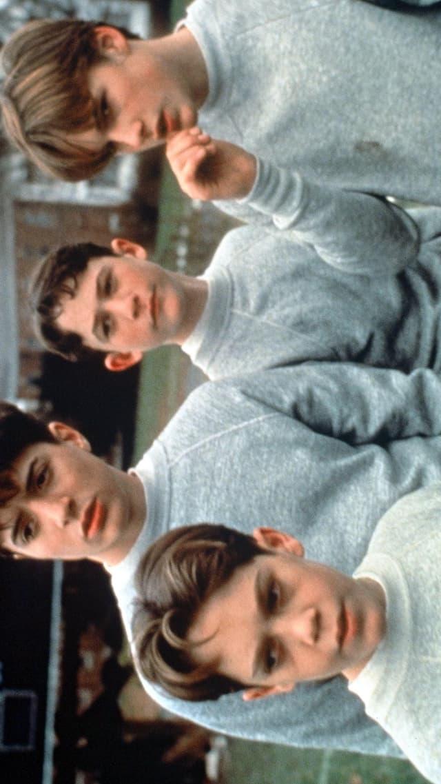 Drie Knaben in einheitlicher grauer Kleidung.