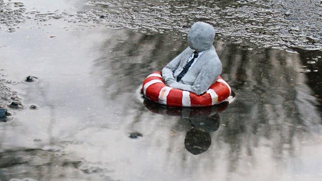 Die Skulptur eines kleinen Männchens in einem Schwimmring dümpelt in einer Pfütze.